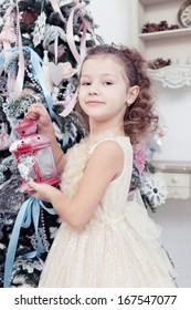 beautiful little girl holds a lamp in hand near a Christmas fir-tree