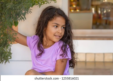 A beautiful little girl holds on to a branch while leaning on a wall looking away. Wearing a solid color light purple shirt with shabby chic messy hair is a look all her own.