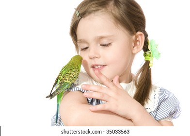 The beautiful little girl holds Parrot and smiles on white background close up isolated