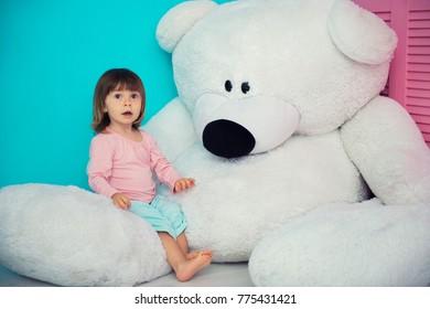 Beautiful little girl hugging big white teddy bear.