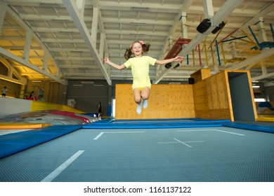 beautiful little girl jumping on a trampoline in the entertainment center