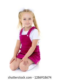 Beautiful little girl kneels in the studio on a white background. The concept of beauty and fashion, children's emotions. Isolated.