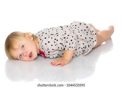 Beautiful little girl lies on the floor on a white background. The concept of a happy childhood, well-being in the family. Isolated.