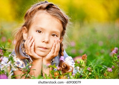 Beautiful little girl lies on green lawn