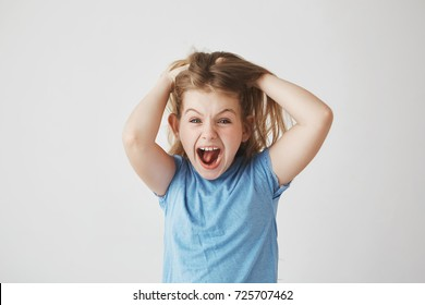 Beautiful little girl with light hair screaming loudly, holding hair with hands, being scared with big spider on the wall in bedroom.