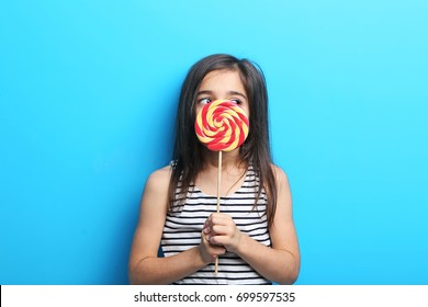 Beautiful little girl with lollipop on blue background