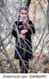 Beautiful little girl with long brunette hair, dressed in dark velvet dress walks in fall forest with handmade bear toy. Halloween horror,  ghost or spirit of child in twilight
