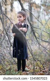 Beautiful little girl with long brunette hair, dressed in black velvet dress walks in fall forest with handmade bear toy. Halloween horror,  ghost or spirit of child in twilight