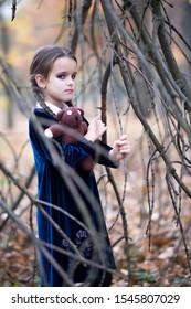 Beautiful little girl with long brunette hair, dressed in dark blue velvet dress walks in fall forest with handmade bear toy. Halloween horror,  ghost or spirit of child in twilight