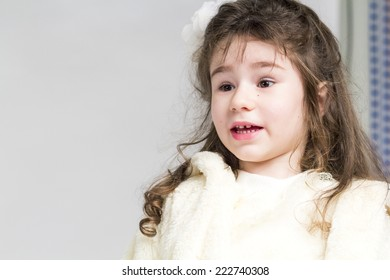 Beautiful little girl with long, curly hair and beige dress posing with light grey background
