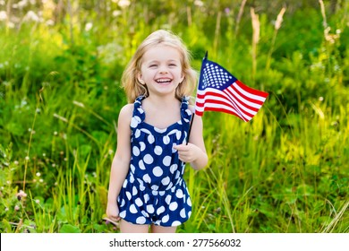 Beautiful little girl with long curly blond hair with american flag in her hand laughing on sunny day in summer park. Independence Day, Flag Day concept
