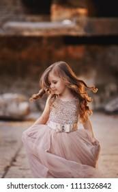 beautiful little girl with long hair in elegant brown dress run in beautiful place
