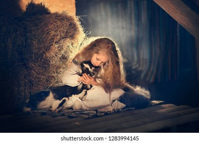 Beautiful little girl with long hair with a little lamb in the hayloft in Russia. Image with selective focus and toning