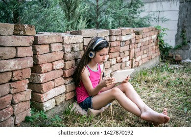 Beautiful Little Girl with Long Hair and Headphones is Sitting on the Ground, lawn to the Brick Wall. She is Looking at her Tablet and Listening to Music During a hot Summer Day.