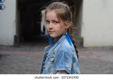Beautiful little girl with long plait in the old town Riga