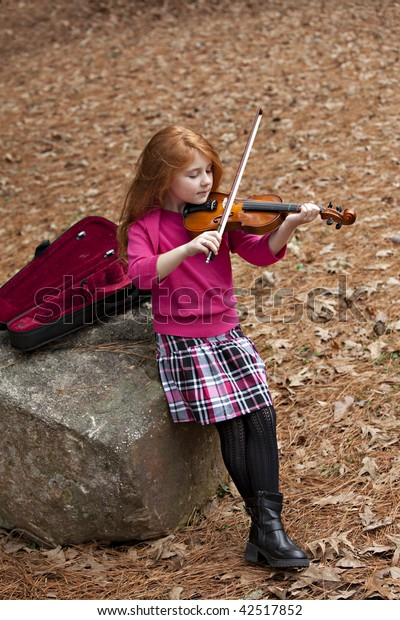 Beautiful little girl with long red hair in pink sweater outdoors practicing her violin among the Fall leaves while sitting on large rock