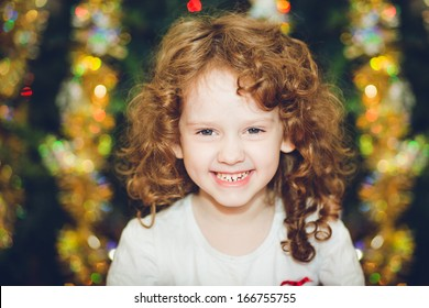 Beautiful little girl looking at the camera and smiles on the background of of the Christmas tree