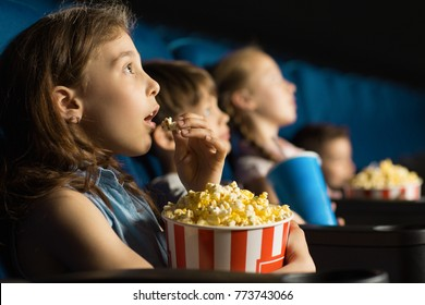 Beautiful little girl looking fascinated eating popcorn watching a movie at the local movie theatre snack bucket junk food tasty childhood entertaining entertained emotions kids concept