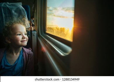 Beautiful little girl looking out train window outside, while it moving. Going on vacations and traveling by railway in summer. Sunset time.