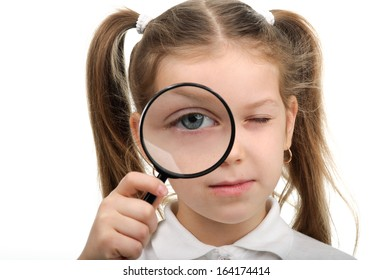 Beautiful little girl looking through a magnifying glass.