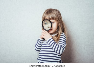 Beautiful little girl looking through a magnifying glass