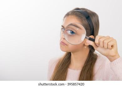 Beautiful little girl looking through a magnifying glass. Funny teen looking through a magnifying glass