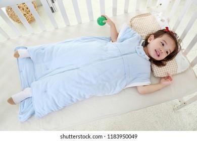 beautiful little girl lying in bed in her sleeping bag