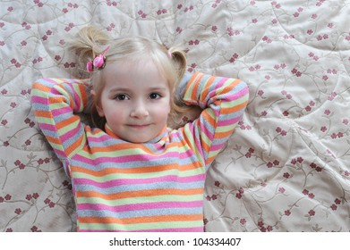 Beautiful little girl lying on bed at house