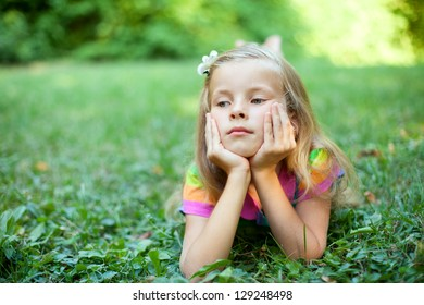 Beautiful little girl is lying on the green grass