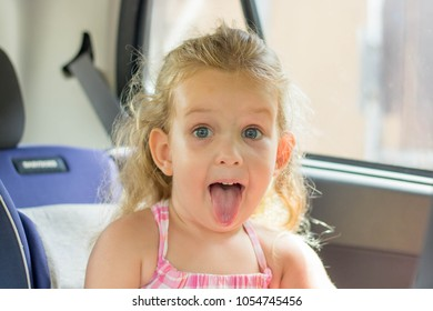 Beautiful little girl is making funny face in baby car seat