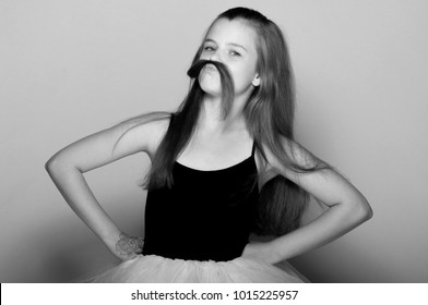 Beautiful little girl making a mustache from her hair funny, isolated on white background. Black and white photo