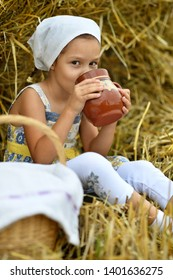 Beautiful little girl with milk in field at summer