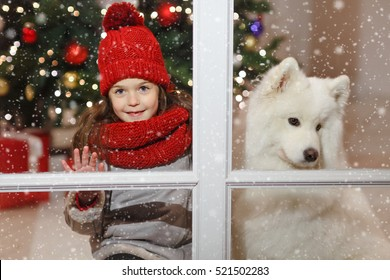 Beautiful little girl near a big white dog in Christmas street decorations for the window frame. There is white snow.
