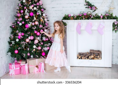 beautiful little girl near a Christmas tree holding a Christmas ball at home on Christmas morning , the new year celebration