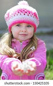beautiful little girl near a flowering tree
