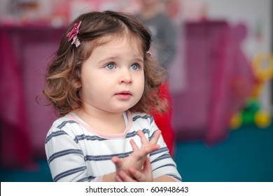 Beautiful little girl in the nursery shows that sick handle