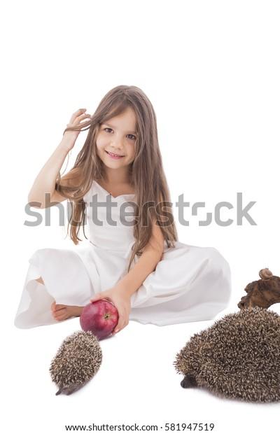 Beautiful little girl offering an  apple  to little  hedgehog