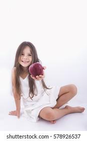 Beautiful little girl offers apple