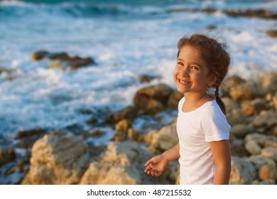 Beautiful little girl on the beach at sunset