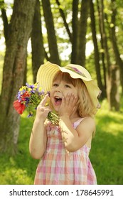 a beautiful little girl on nature with a bouquet of flowers