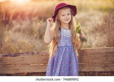 Beautiful little girl outdoor in hat over meadow