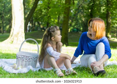 Beautiful little girl in a park on a picnic with straw basket and hat. Spring sunny concept. Happy mothers day. Happy loving family. Mother and daughter. Lifestyle concept.