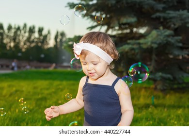 Beautiful little girl in the Park playing with soap bubbles