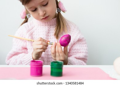 A beautiful little girl with pink bunny ears (hare) is preparing for the celebration of Easter, painting a wooden egg in pink colore. Light background. Free space for text.