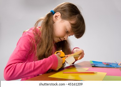 beautiful little girl in a pink cardigan carves figures out of colored paper
