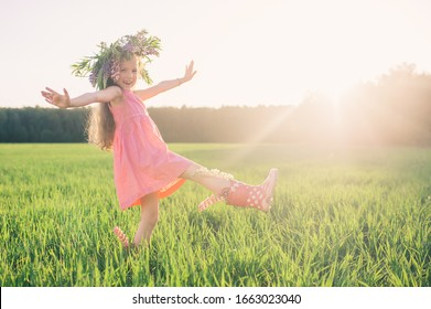 Beautiful little girl in a pink dress and boots with a wreath of flowers on her head joyfully jumps in a field with green grass. The sun's rays flood the girl