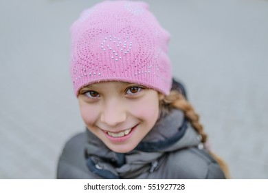 Beautiful little girl in pink hat and gray jacket.