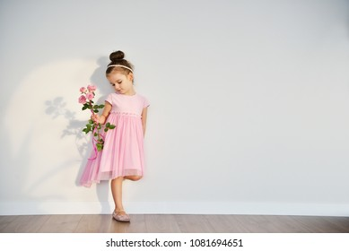 Beautiful little girl with pink rose flowers weared pink dress is standing near the wall.