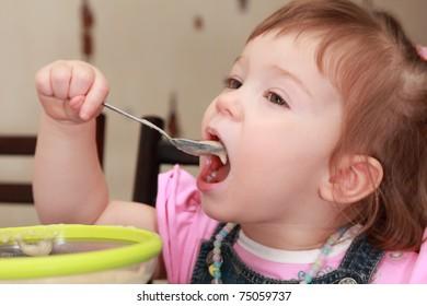 beautiful little girl in pink shirt eating porridge, yellow plate