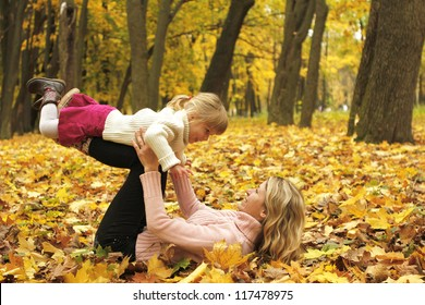 beautiful little girl play with her mother in the autumn forest